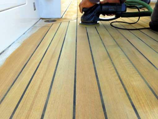 Marine engineer sanding a deck